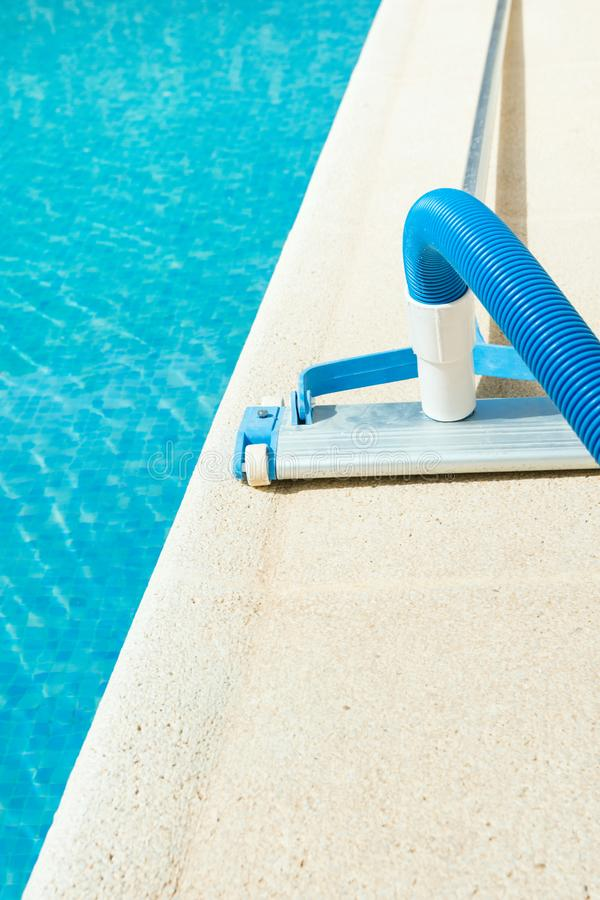 Aspirador manual de la piscina en la cubierta de piedra Día soleado brillante del verano Concepto del servicio de la limpieza del fotografía de archivo libre de regalías