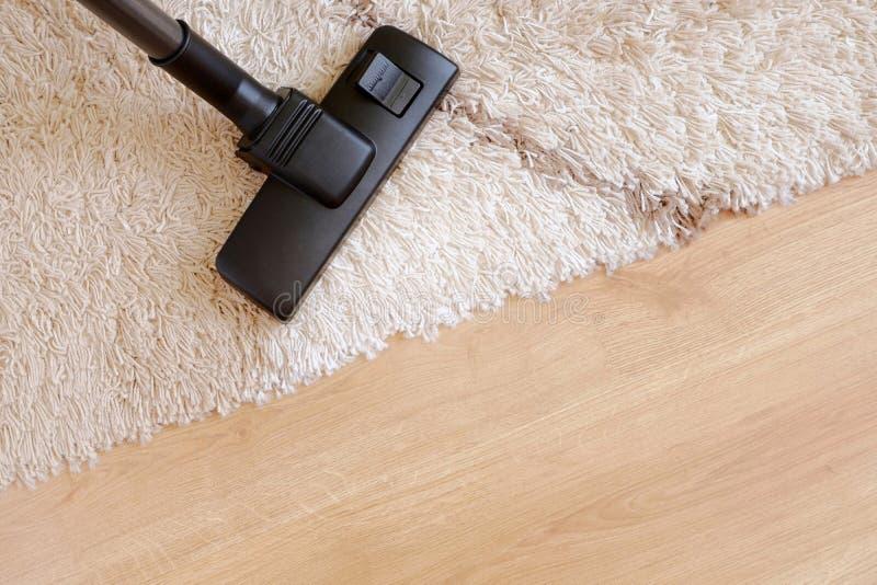 Aspirador moderno en un entarimado de madera de la alfombra beige imagen de archivo