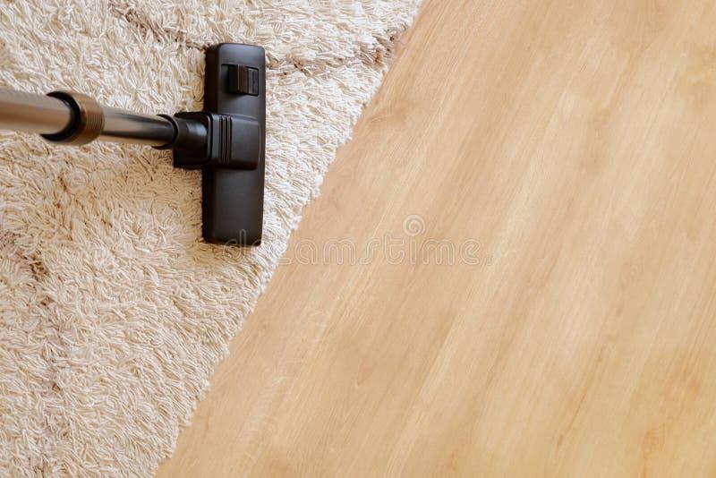 Aspirador moderno en un entarimado de madera de la alfombra beige foto de archivo
