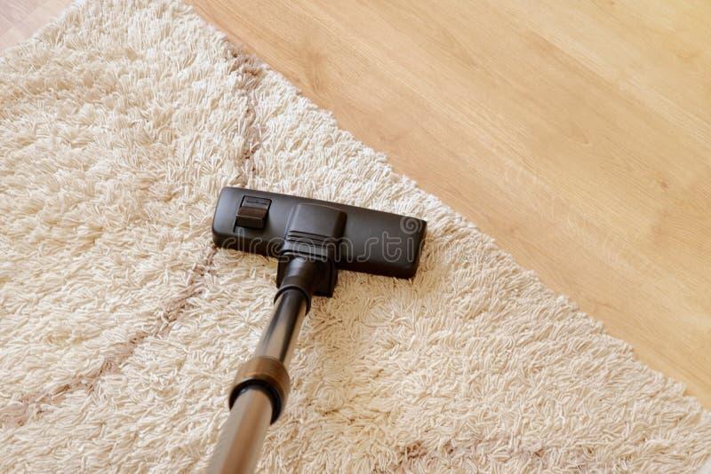 Aspirador moderno en un entarimado de madera de la alfombra beige imagenes de archivo