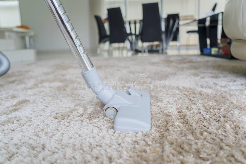 Aspirador que quita la suciedad en la alfombra blanca imagen de archivo