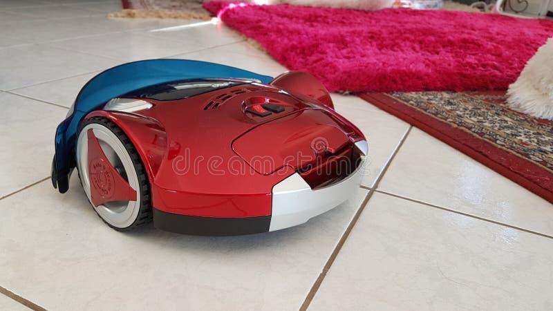 Aspirador robótico en el piso y la alfombra imagenes de archivo