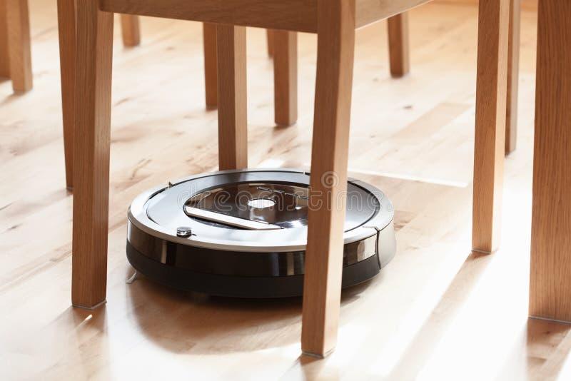 Aspirador robótico en la limpieza elegante del piso de madera laminado técnica imagenes de archivo