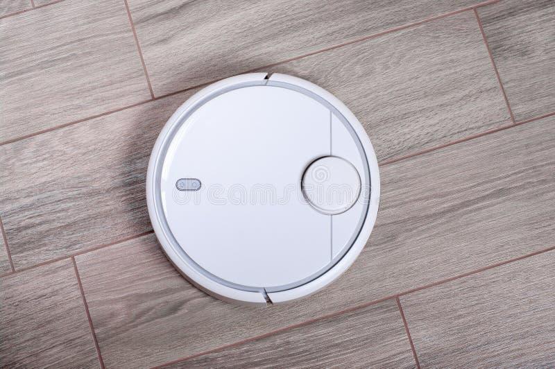 Aspirateur automatisé de robot sur le plancher de tuiles robotiques futés automatisent le ménage sans fil de technologie de netto photos libres de droits