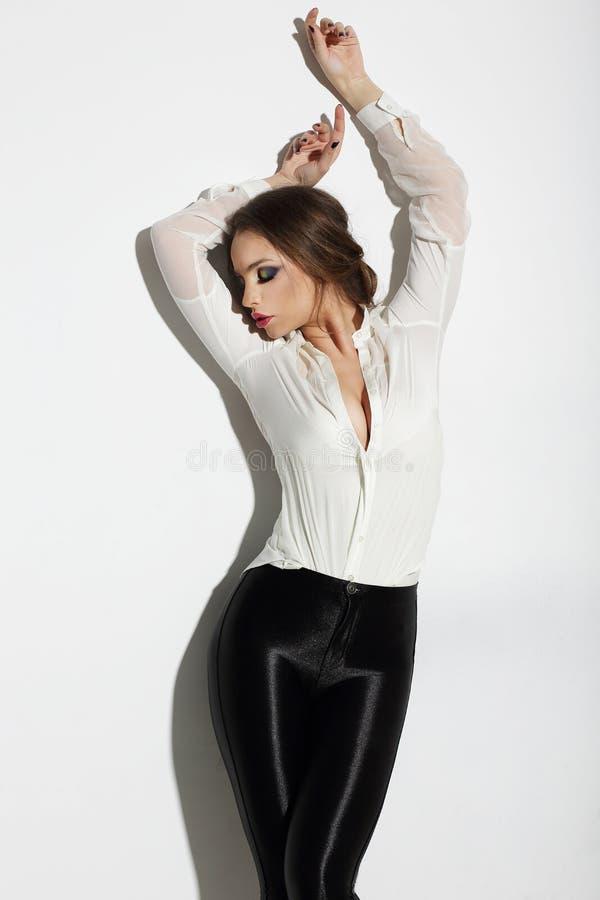 aspiration Verlockende Frau in der weißen Bluse mit den Händen angehoben lizenzfreie stockbilder