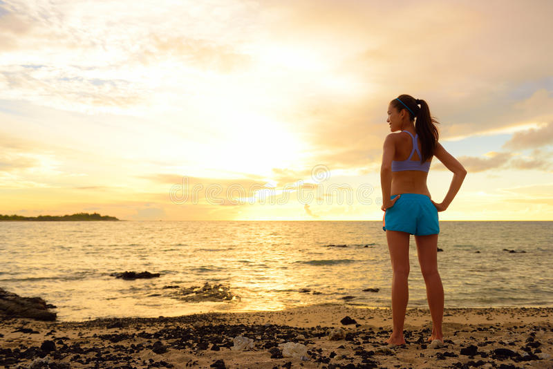 Aspirations - woman looking away with inspiration. Fitness woman after run in sunset on beach looking at ocean feeling peaceful and serene relaxing during stock photography
