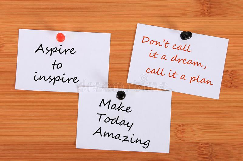 `Aspire to inspire`. `Don`t call it a dream, call it a plan.` `Make Today Amazing`. Note pin on the bulletin board. `Aspire to inspire`. `Don`t call it a dream stock photography