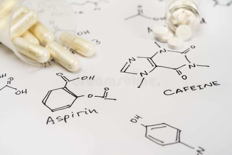 Aspirin en cápsulas y caffein en tabletas foto de archivo