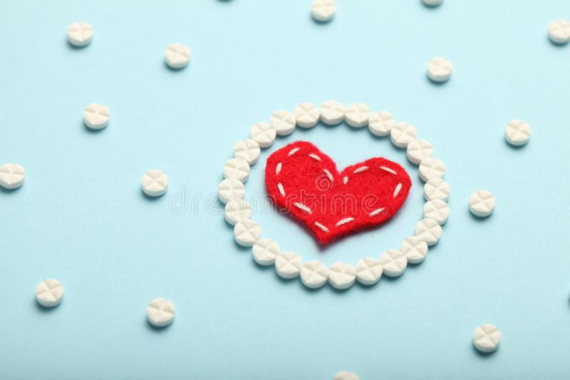 Aspirin tablets and red heart. Cardiology and medicine, healthcare and pharmacy concept.  stock photo