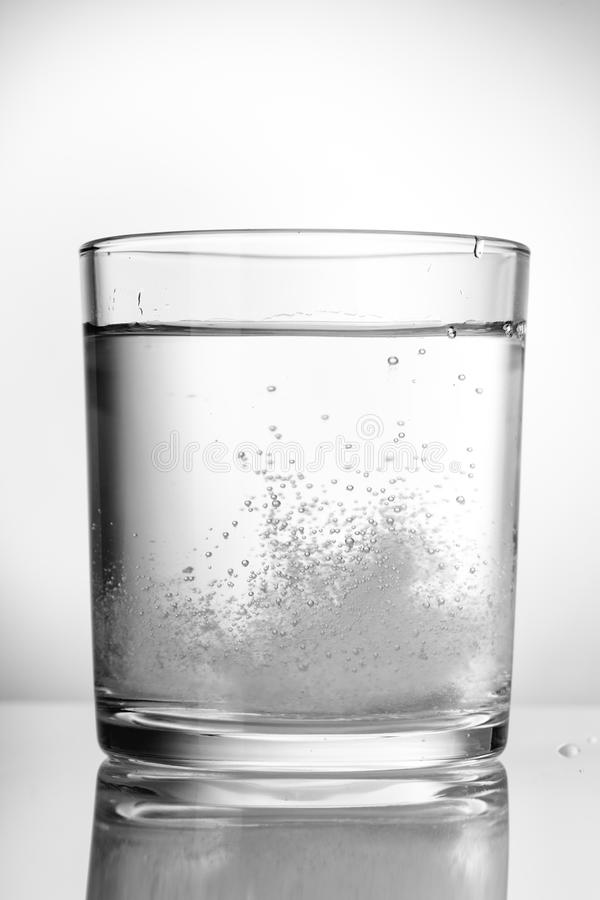Aspirin, vitamins, fizzing in a glass of water. Close up stock images