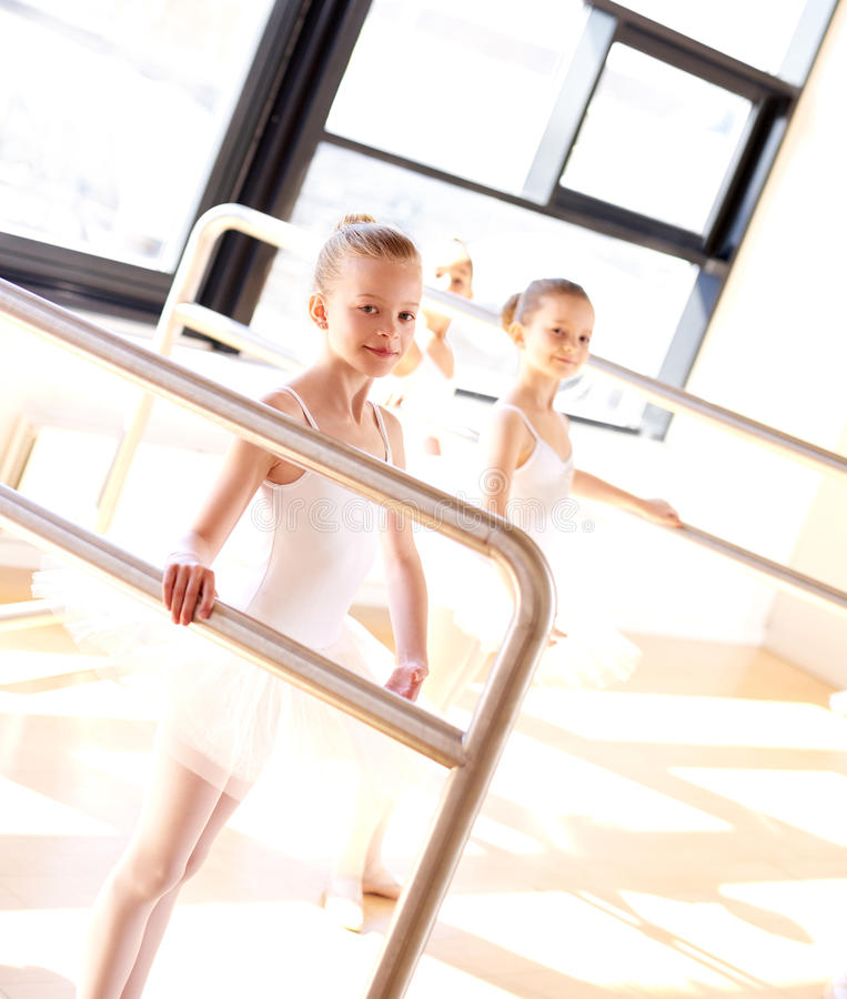 Aspiring young ballerinas practicing at the bar royalty free stock images