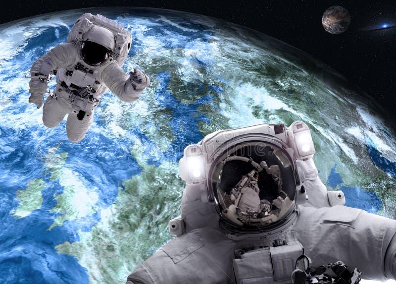 Asrtonauts i yttre rymd n?ra jordar en kontakt och f?rd?rvar planeter fotografering för bildbyråer