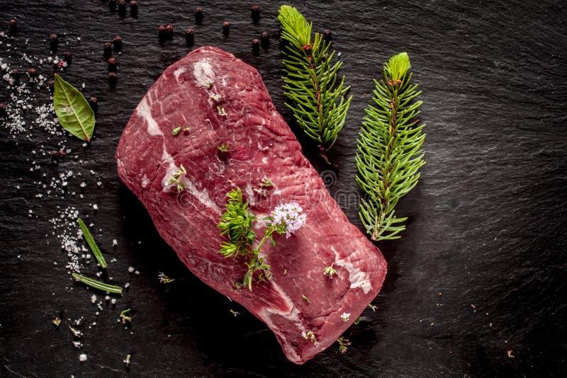 Assado de carne cru temperado com ervas frescas fotografia de stock