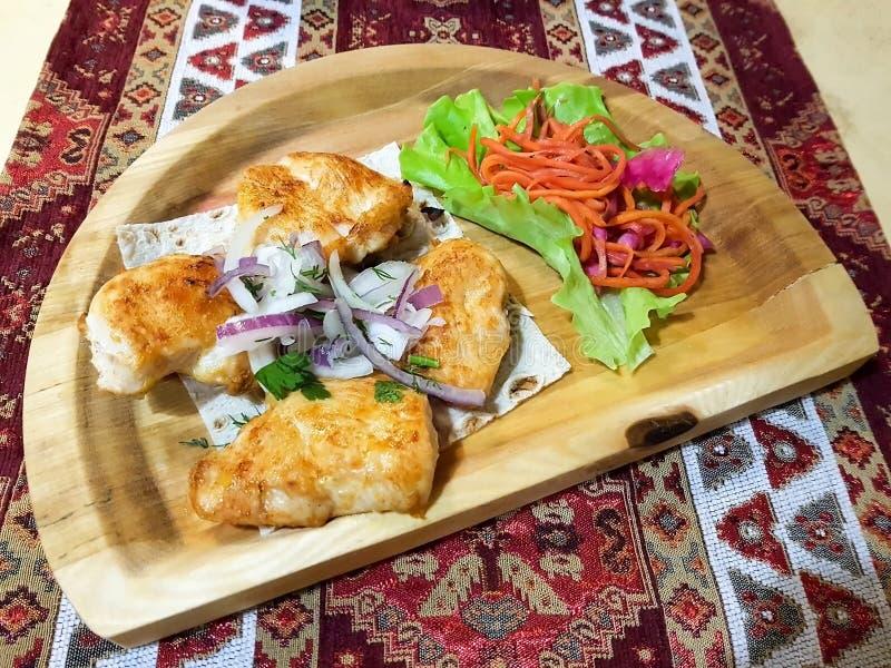 Assado delicioso em uma placa de madeira com cenouras fotos de stock