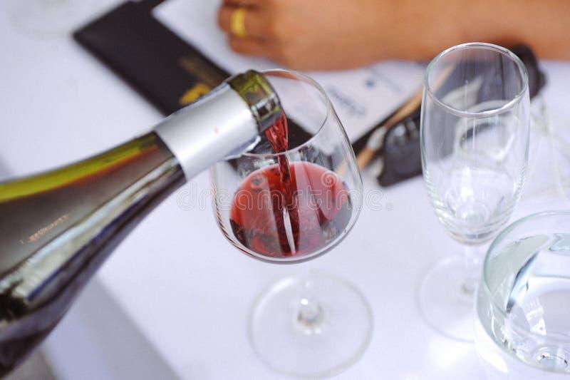 Assaggiando il vino bianco versi dentro un vetro, versante il vino bianco da vino fotografia stock libera da diritti