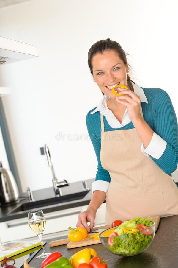 Assaggio della giovane donna che prepara il pranzo delle verdure della cucina fotografia stock libera da diritti