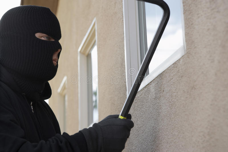 Assaltante Breaking Into House foto de stock