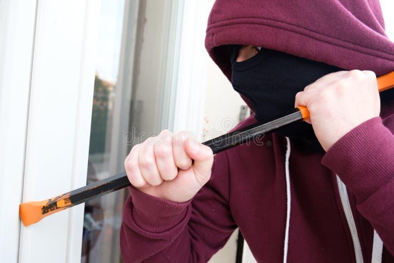 Assaltante encapuçado que força a janela para roubar na casa fotografia de stock royalty free