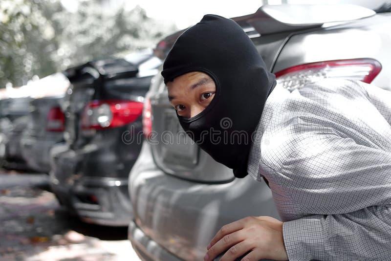 Assaltante mascarado que veste um passa-montanhas pronto ao roubo contra o fundo do carro Conceito do crime do seguro imagens de stock royalty free
