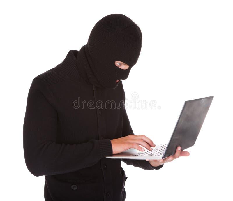 Assaltante que usa o portátil fotografia de stock