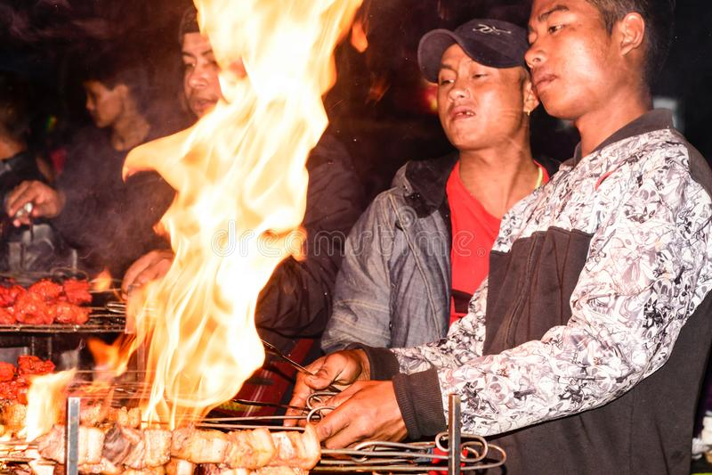 Assam, la India 6 de mayo: Un hombre que prepara kebab en parrilla de la barbacoa sobre el carbón de leña Rosbif en parrilla del  foto de archivo
