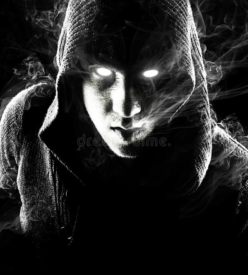 Assassin émotif, jeune et attirant sur le fond noir images stock