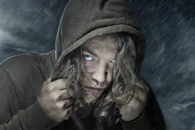 Assassin. Portrait of the man under the rain. He could be assassin, thief, hitman, stranger, etc stock photo