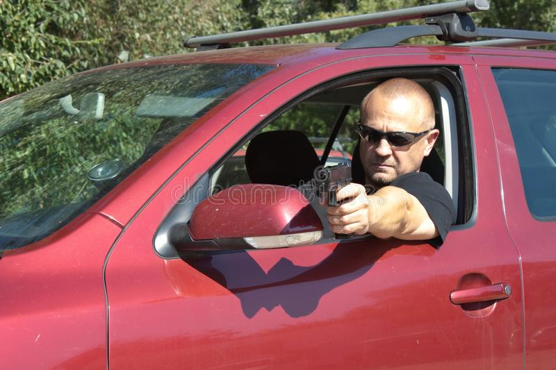 Assassin shooting from a moving car stock photography