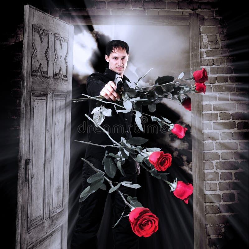 Assassino dell'uomo con la pistola e le rose rosse fotografie stock