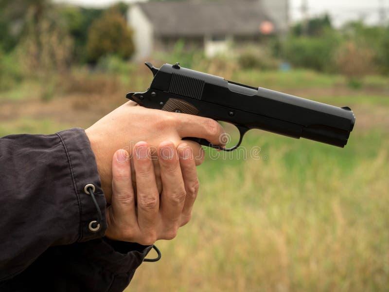 Assassino que guarda uma arma, mão que mantém armas isoladas no fundo branco imagem de stock