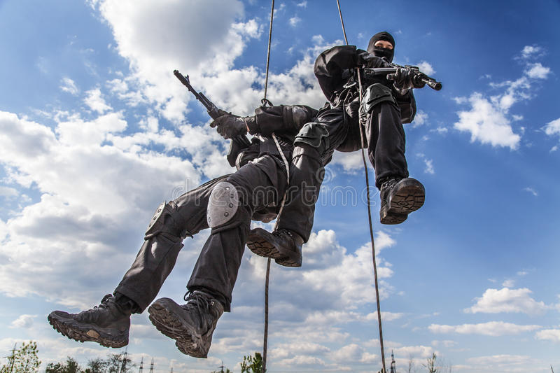 Assault rappeling. Special forces operators during assault rappeling with weapons royalty free stock photography