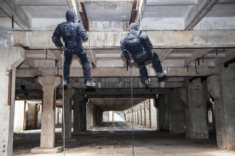Assault rappeling. Special forces operators during assault rappeling with weapons royalty free stock image
