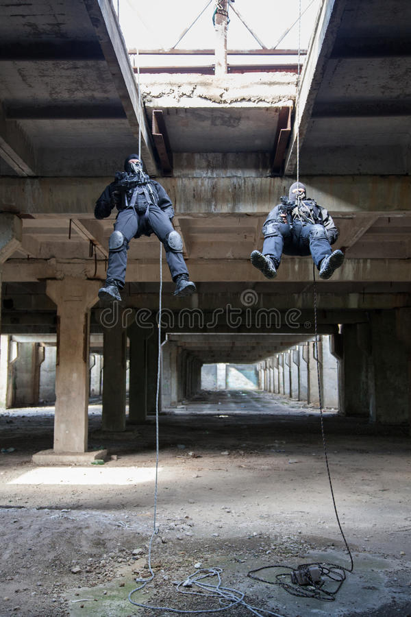 Assault rappeling. Special forces operators during assault rappeling with weapons royalty free stock images