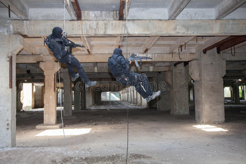 Assault rappeling. Special forces operators during assault rappeling with weapons stock photography