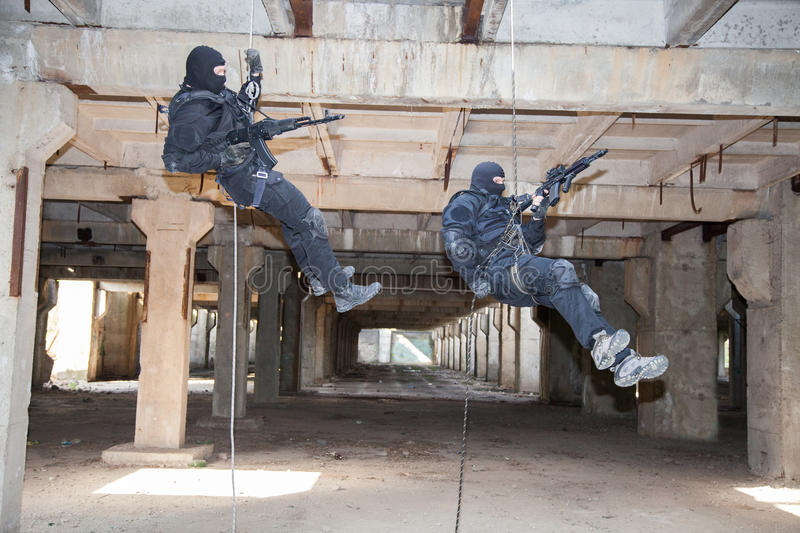 Assault rappeling. Special forces operators during assault rappeling with weapons stock image