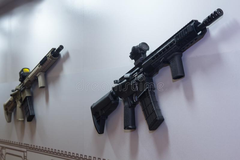 An assault rifle hangs on a wall in a gun shop. Weapons royalty free stock photo