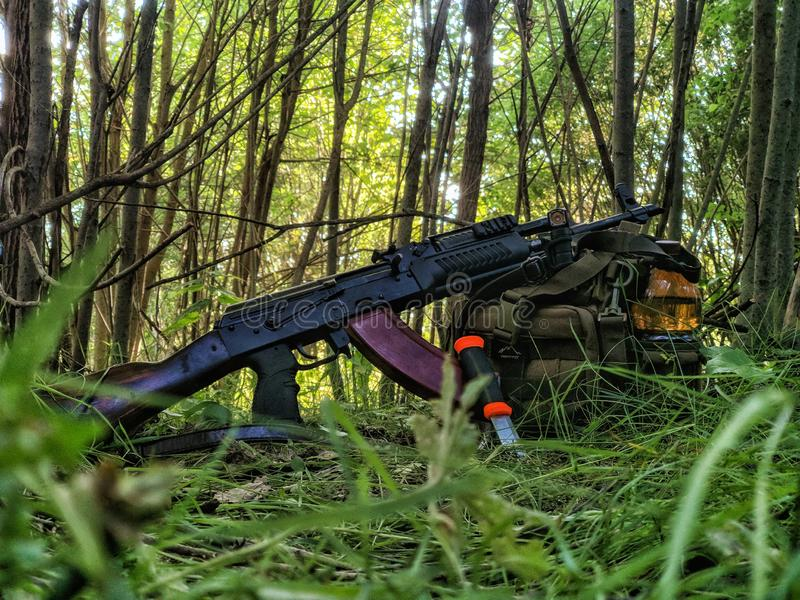Assault rifle, knife, tactical backpack, flashlight in the forest stock photos