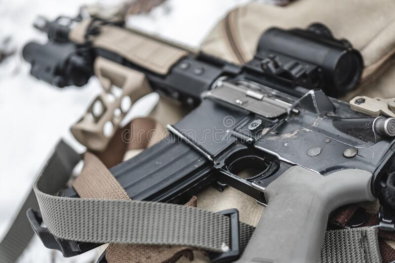 An assault rifle lies on a military briefcase. Close up stock photos