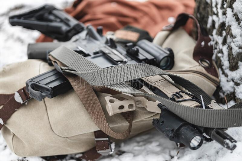 An assault rifle lies on a military briefcase in winter time. Close up stock images