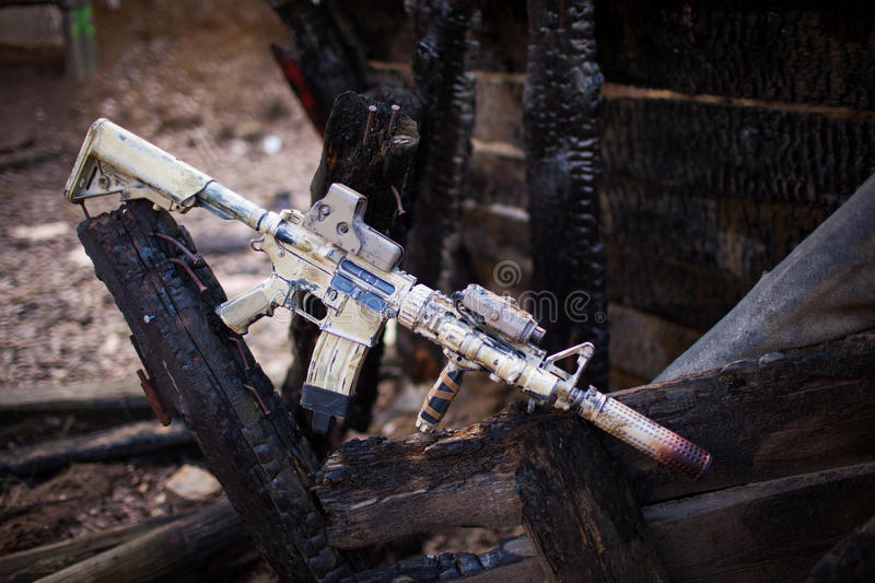 Assault Rifle, painted in sand color. Assault Rifle, painted in sand color on the background of the burnt logs. Airsoft royalty free stock image