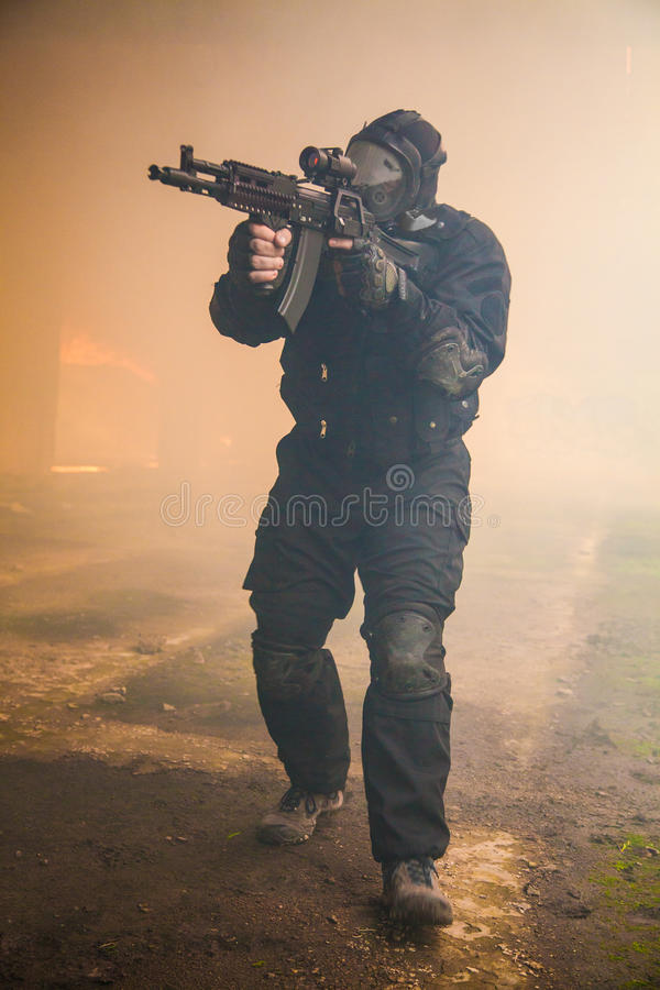 Assault in the smoke. Special forces operator in black uniform in the smoke stock image
