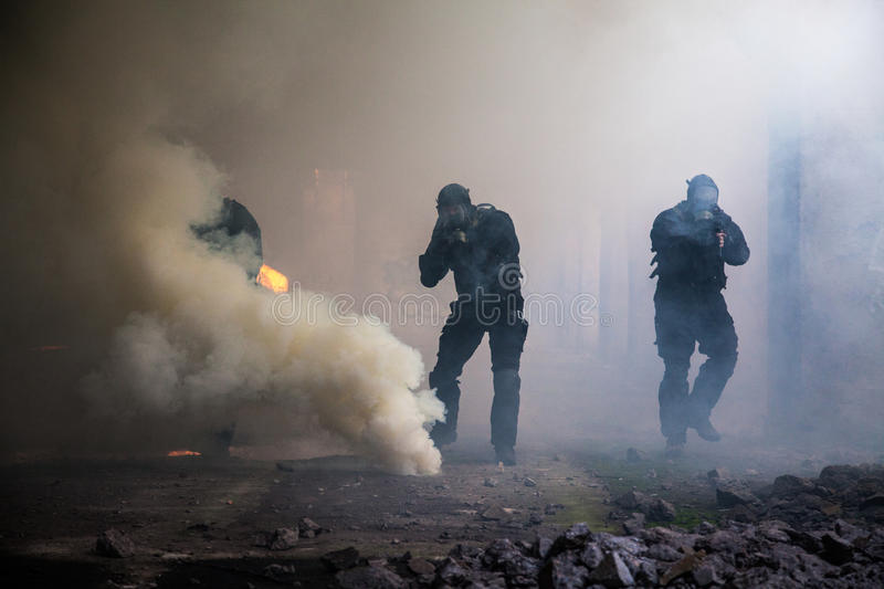 Assault in the smoke. Special forces operator in black uniform in the smoke stock photos