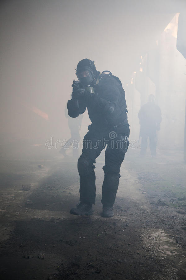 Assault in the smoke. Special forces operator in black uniform in the smoke royalty free stock photo