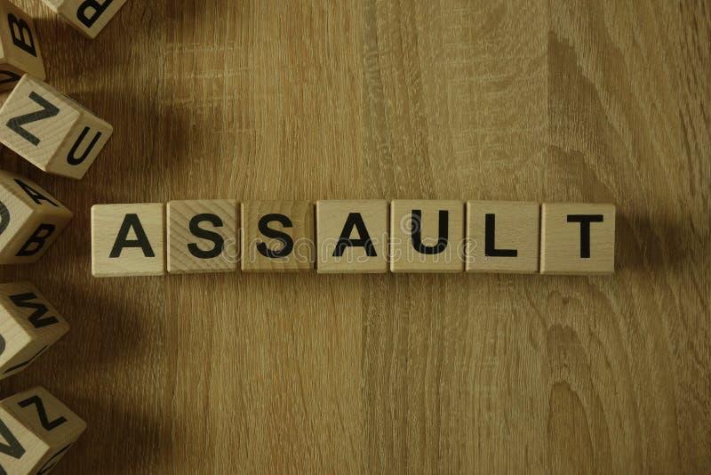 Assault word from wooden blocks. On desk stock image