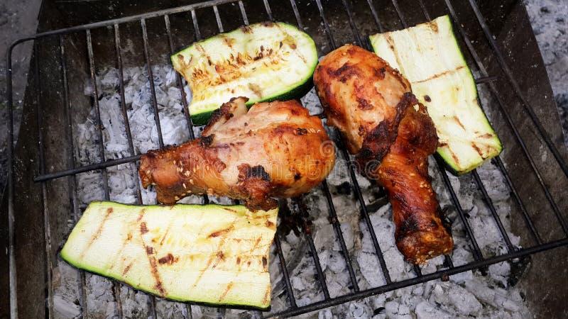 Asse os pés de galinha e o abobrinha da fatia na grade do fogo imagens de stock