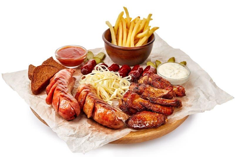 Asse a placa com carne, batatas fritas e molho picante imagem de stock royalty free
