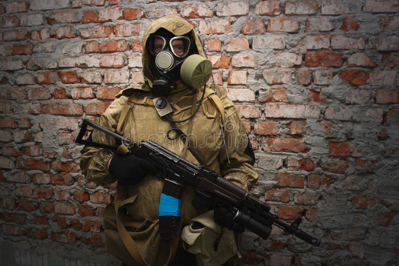 Assediador na máscara de gás com a arma perto da parede de tijolo imagens de stock royalty free