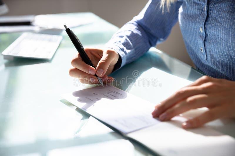 Assegno di firma della donna di affari fotografia stock