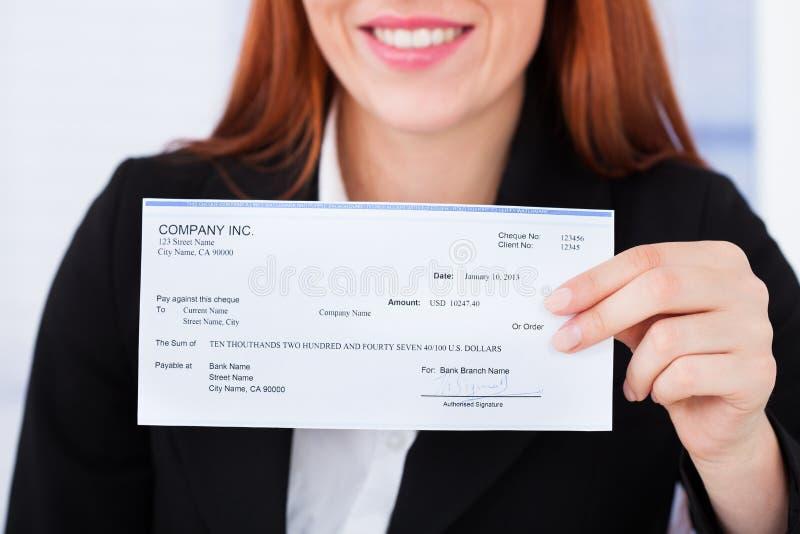 Assegno sorridente della tenuta della donna di affari immagini stock