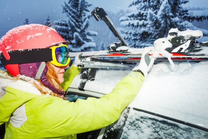 A asseguração fêmea do esquiador esquia para telhar os trilhos do carro fotografia de stock